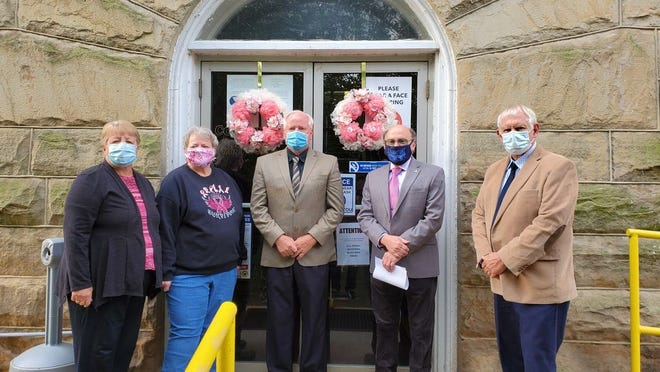 Shirley Tasker, CEOS Family Committee chairperson; Nancy Kelly, Limestone CEOS Club president, and Mineral County Commissioners Jerry Whisner,  Dr. Richard Lechliter, and Roger Leatherman stand in front of the wreaths placed on the courthouse doors in observance of Breast Cancer Awareness Month.