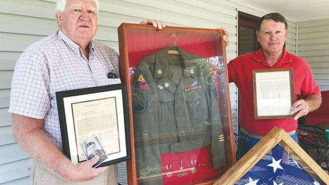 Bill and Joe Casto with their father's WWII uniform, awards, and flag that draped his coffin.