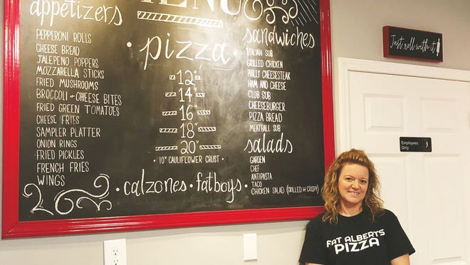 Amanda Smith shows off the Fat Albert's hand-written menu signboard.