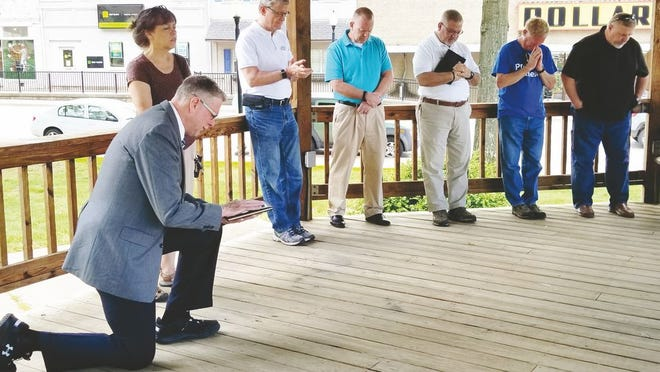 On bended knee, Freewill Baptist Church Pastor Chris Skeens, leads local ministers in a prayer during the 2019 National Day of prayer.