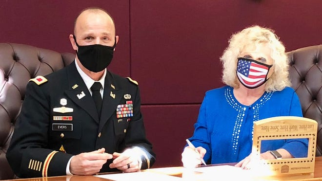 Colonel Jason Evans of the Army Corps of Engineers and Mayor Carolyn Rader sign grant paperwork for $1,050,000.
