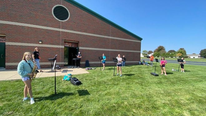 Washington Middle School band members practice social distancing and music under the direction of band director Julie Donnell during an outdoor practice last week.
