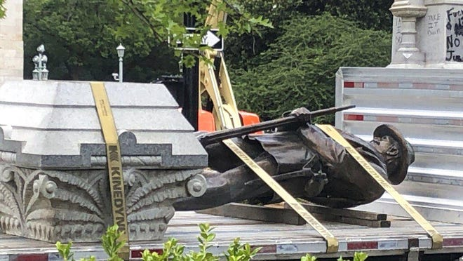 The statue of a Confederate soldier and plinth sit on a flatbed truck at the Old Capitol in Raleigh June 21. After protesters pulled down two smaller statues on the same monument Friday, North Carolina Gov. Roy Cooper ordered the removal of several other monuments to the Confederacy, citing public safety concerns.