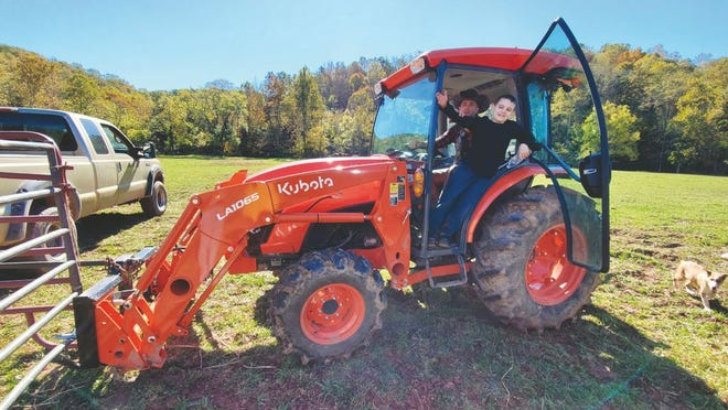 Pictured behind the wheel of his new MX6000 Kubota tractor is Josh Nelson with his farm-hand son, Elijah, enjoying the new machine.