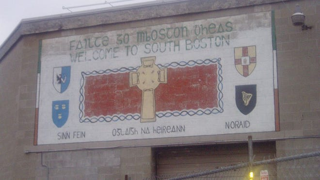 """A mural in South Boston says """"Welcome to South Boston"""" in English and """"Faitre go mBoston dheas"""" in Irish.  Also shown is a Celtic cross, the coats of arms of the Provinces of Ireland and the words """"Sinn Fein,"""" """"Irish Republican Army"""" and NORAID."""" This mural has been torn down along with the building to make way for resident housing. Photo from/wikipedia.org"""