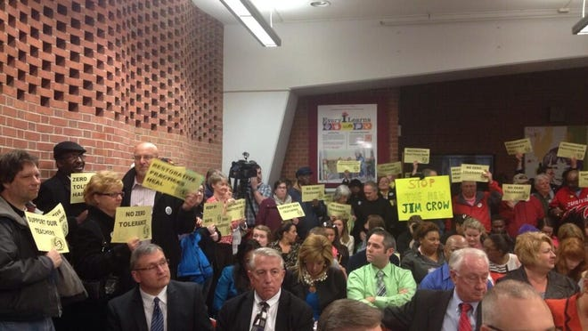 """""""Zero Tolerance Harms"""" and """"Restorative Practices Now"""" are among signs at Monday's Jefferson County Public Schools board of education meeting."""