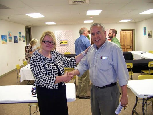 The Membership Chair baton is shown being passed from Laura Becker, left, to Ray Hoover.