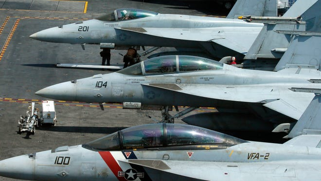In this March 3, 2017 file photo, a row of F18 fighter jets are shown on the deck of the U.S. Navy aircraft carrier USS Carl Vinson (CVN 70) off the disputed South China Sea. Navy officials say a fighter jet has crashed off the coast of Key West, Florida, and rescue efforts are underway. The officials say the F/A-18 Hornet's two crew members ejected and are based out of Naval Air Station Oceana, in Virginia Beach, Va.