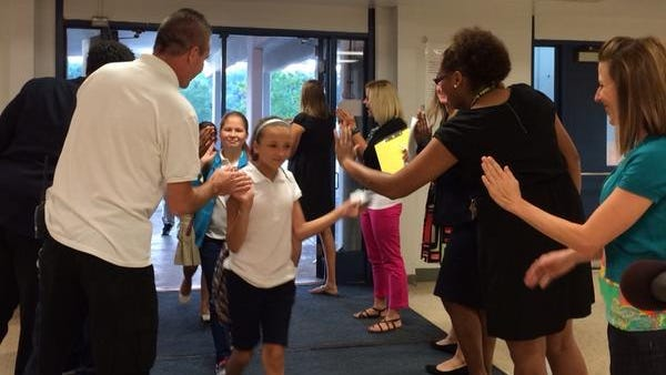 Kids receive a warm welcome, complete with cheers and high fives, as they arrive at Robert Frost Elementary