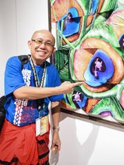 "Local artist Rolly Zepeda shows one of his pieces on display at the FestPac visual arts exhibit at the Guam Museum on May 26. The theme for this painting, which is a scale model for a larger upcoming piece, is ""Turtles coming home,"" said Zepeda."