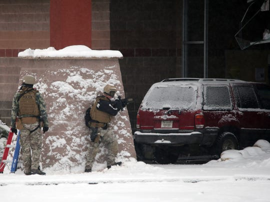 Law enforcement officers take cover at the front entrance of Big Bear Sports Center during a standoff between law enforcement and a man who barricaded and armed himself inside the building Saturday, November 4, 2017.
