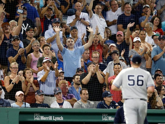 Fans react as New York Yankees' Jonathan Holder (56) leaves the field after being removed during the fourth inning of the team's baseball game against the Boston Red Sox in Boston, Thursday, Aug. 2, 2018.