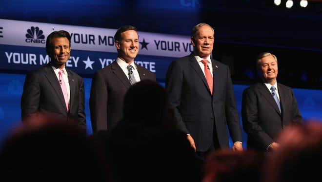 Bobby Jindal, Rick Santorum, George Pataki and Lindsey Graham take the stage for the CNBC Republican presidential debate at University of Colorado's Coors Events Center on Oct. 28, 2015, in Boulder, Colo.