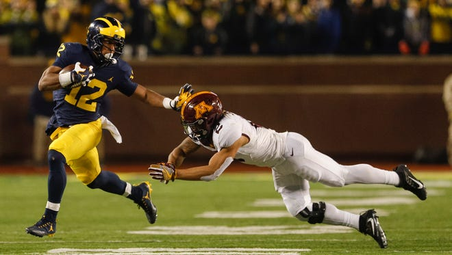 Nov. 4: Michigan running back Chris Evans (12) is and chased by Minnesota defensive back Jacob Huff (2) during the first half of U-M's 33-10 win. Evans had 191 yards rushing and two TDs.