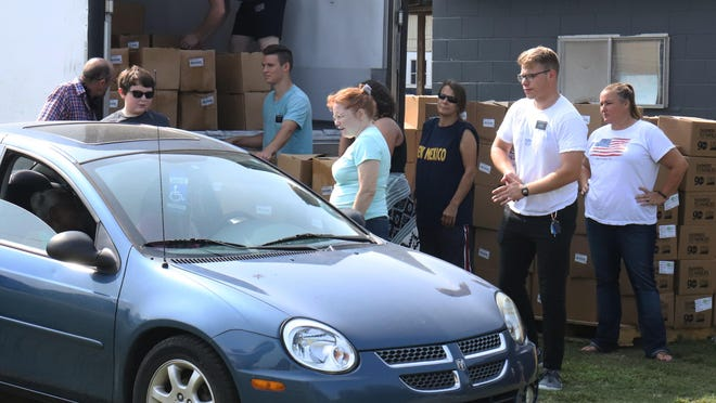 Volunteers load boxes of USDA GoFresh produce into a car, Monday, Sept. 14, during the Pay It Forward - Fort Smith food pantry at 616 N 10th.