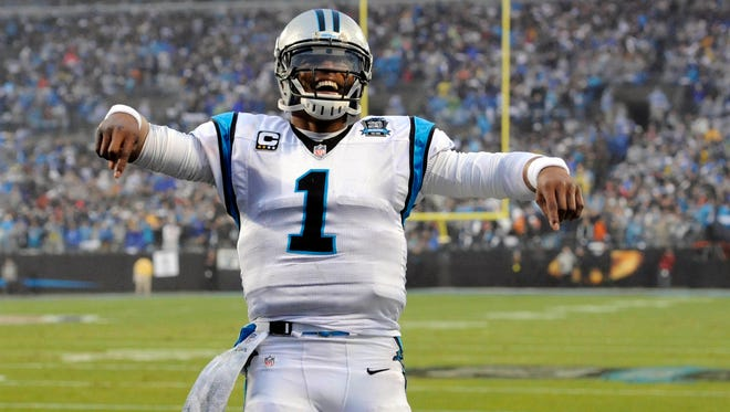 Carolina Panthers quarterback Cam Newton (1) celebrates a touchdown during the first quarter against the Arizona Cardinals in the 2014 NFC Wild Card playoff football game at Bank of America Stadium.
