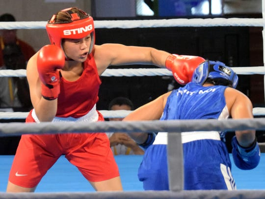 Guam's Gianna Sarusal (red) throws a punch during her bout against Tahiti's Edith Tavanae July 16 at the Caritas Technical School during the Pacific Games in Port Moresby, Papua New Guinea. The winner would advance to the gold medal fight, but Sarusal lost by decision against Tavanae in a competitive match. She picked up a bronze for Guam - Guam's 13th medal of the Games.