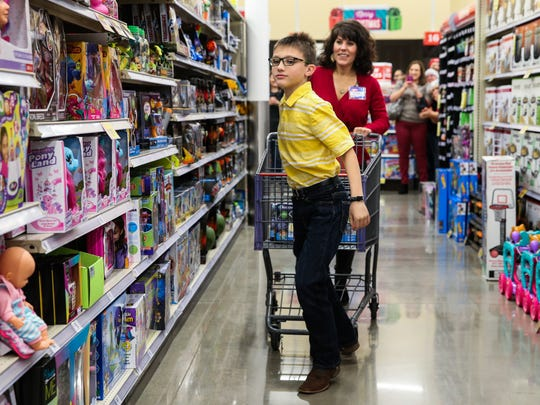 Stetson Coffey, 9, looks for toys as Stephanie Reisner, H-E-B administrative assistant, pushes the cart on a shopping spree Tuesday, Dec. 19, at San Angelo's H-E-B #2.