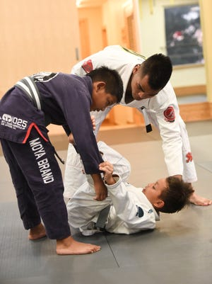 Luis Reyes, owner and instructor of Figo Gym in HagŒt–a, instructs his evening Jiu-Jitsu class held at the gym on July 20.  Reyes has recently been promoted from brown, to black belt.