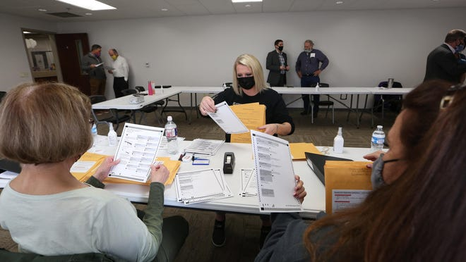 April Hoschouer, center, with Joan Brown, left, and Nancy Hardon, right, pull ballots out of their envelopes during canvassing Thursday morning at the Reno County Courthouse Annex.