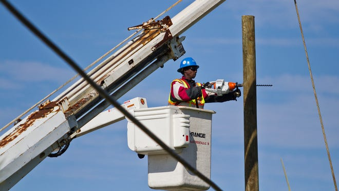 An electrical worker drills a hole through a pole during the restoration process Monday morning after a tornado which struck Saturday evening left a large number of residents without power. Electrical workers on power lines were a common scene this morning along the tornado stricken area of Beach Parkway and Chiquita Boulevard in Cape Coral. Electric companies were working quickly to restore power throughout the area.