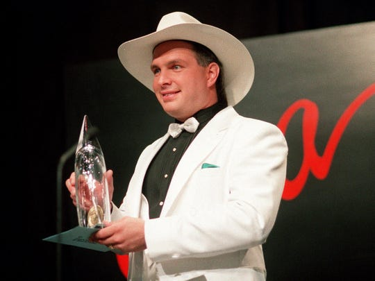 Garth Brooks won the Academy of Country Music's Entertainer of the Year award from 1990 to 1993 and 1997 and 1998. Here, he is with one of his four awards from the CMA Awards show, including Entertainer of the Year, in 1991