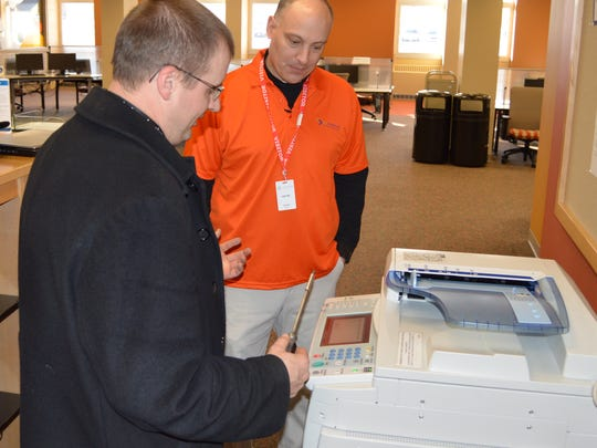 EO Johnson Business Technologies service technician Terry Boneske, left, instructs Wausau Region Chamber of Commerce President/CEO Aaron Kapellusch on copy machine repairs.