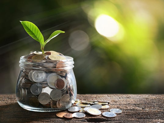 Image of pile of coins with plant on top in glass