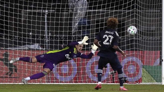 Sporting Kansas City forward Gianluca Busio (27) kicks the winning goal against Vancouver Whitecaps goalkeeper Thomas Hasal during a shootout in extra time of an MLS match early Monday in Kissimmee, Fla.
