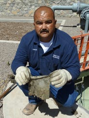 Las Cruces Utilities worker Carlos Almaraz holds up