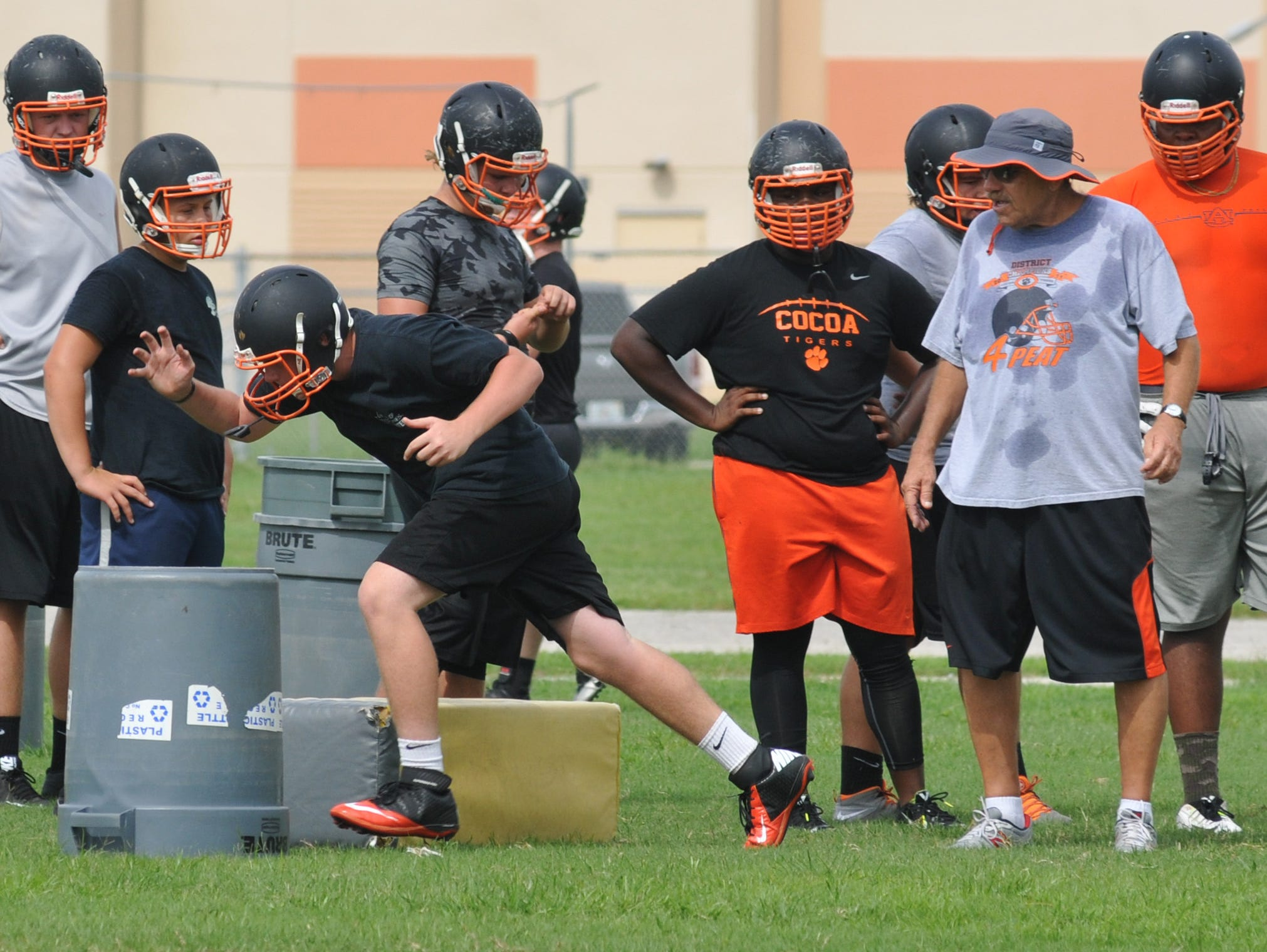 Cocoa offensive line coach Mike Vogt (second from right) works with his linemen.