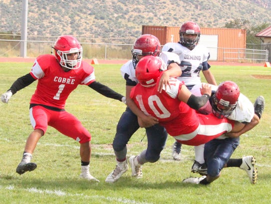 Cobre quarterback Gilbert Soto is twisted during a