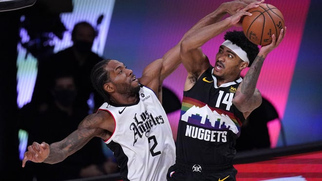 Denver Nuggets' Gary Harris (14) goes up for a shot as Los Angeles Clippers' Kawhi Leonard (2) on Sunday.