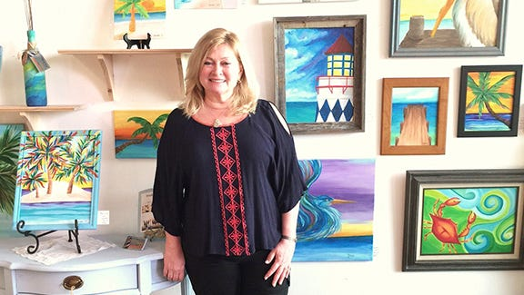 Artist, Maureen Turner, poses proudly in front her displayed work.