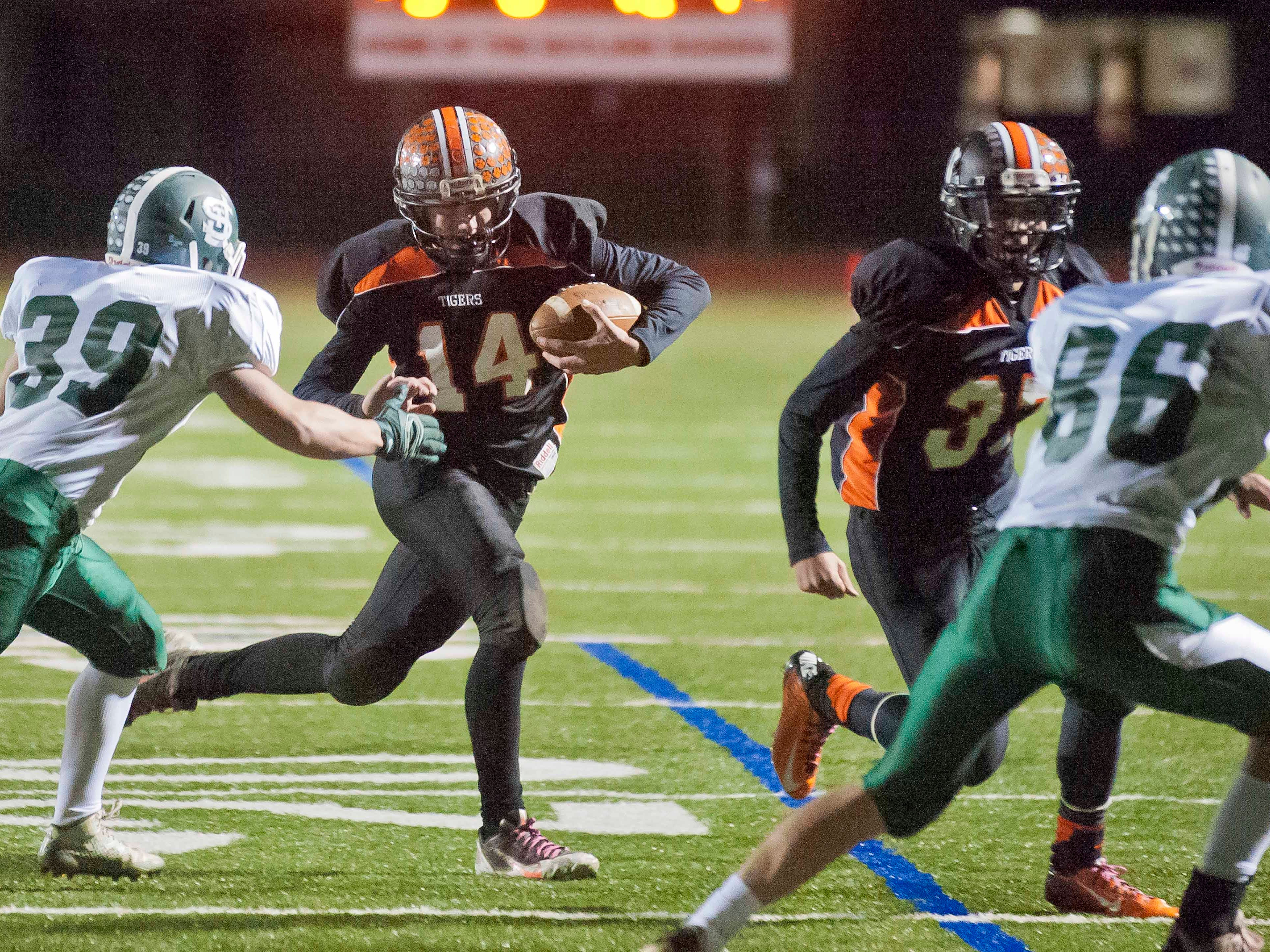 Middlebury's Austin Robinson (14) avoids St. Johnsbury's Ryan Haff, left, on his way to scoring a touchdown in the Division I high school football championship game in Rutland last month. The win sealed the Tigers' second straight crown.