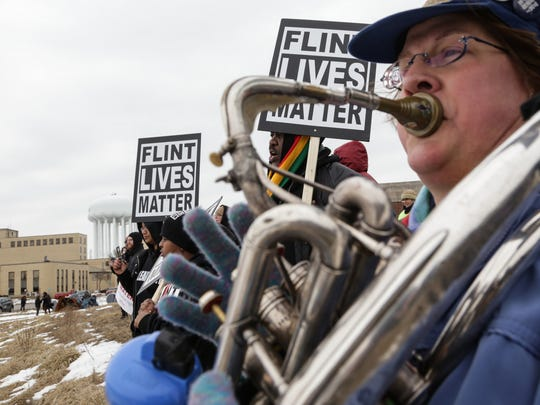 Karen Dunnam of Grand Rapids plays the sousaphone while standing with others at the Flint Water Plant to hear speakers during the Rebuild Flint rally on Friday, Feb. 19, 2016.