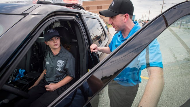 Port Huron Police officer Ryan Sheedy, right, gives direction to Victoria Montgomery during a simulated traffic stop Monday at the Port Huron Police School Youth Academy at Port Huron High School.