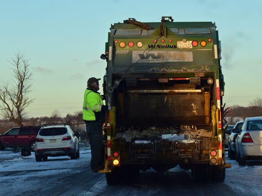 Paul Poe, Waste Management, rides on the back of a truck while collecting recyclables in Chambersburg, Wednesday morning, Jan. 13, 2016. To make it easy for Chambersburg's 11,000 utility customers to do just that, a new single stream recycle program is underway in the borough.