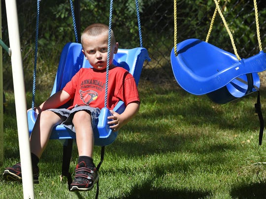 Trent Korpela plays on a swing set in the backyard of his home on July 31 near South Haven.