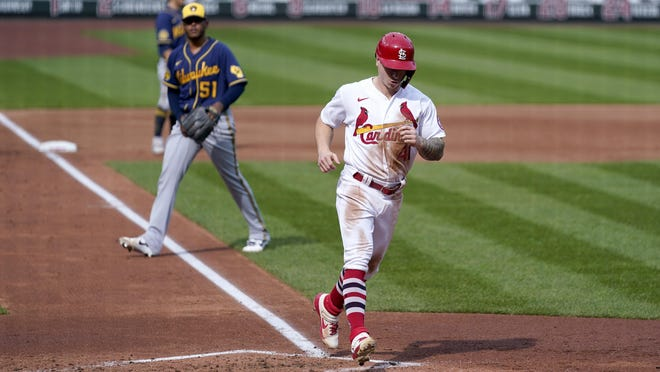 St. Louis Cardinals outfielder Tyler O'Neill, right, scores as Milwaukee Brewers relief pitcher Freddy Peralta (51) watches during the third inning of a game Sunday, Sept. 27,  in St. Louis.