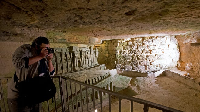 In this photo taken Tuesday, Oct. 14, 2014, a man takes photos of quarries sculptures at the Catacombs in Paris, France. As if visiting the Paris Catacombs in the daytime weren't creepy enough _ soon you can visit the underground maze of skeletons at night, too. The subterranean tunnels, which once gave refuge to smugglers and saints, cradle the bones of some 6 million Parisians from centuries past. (AP Photo/Francois Mori)