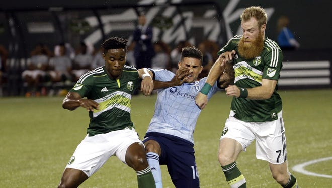 Sporting Kansas City forward Dom Dwyer, middle, battles for the ball with Portland Timbers midfielder George Fochive, left, and defender Nat Borchers during the first half of an MLS soccer match in Portland, Ore., Wednesday, Sept. 9, 2015.