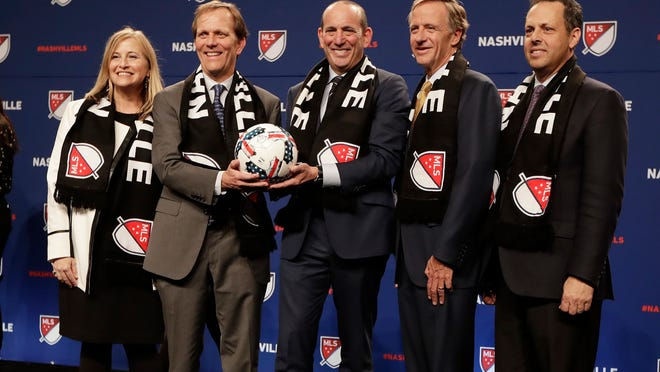 Major League Soccer commissioner Don Garber, center, poses for pictures after announcing that Nashville, Tenn., has been awarded a Major League Soccer franchise Wednesday, Dec. 20, 2017, in Nashville. From left are Nashville Mayor Megan Barry; John Ingram, chairman of Ingram Industries Inc.; Garber; Tennessee Gov. Bill Haslam; and Mark Wilf, of the Wilf family, owners of the Minnesota Vikings NFL football team. (AP Photo/Mark Humphrey)