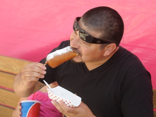 Juan Bravo of Visalia tries a deep fried cheesecake Wednesday at the Tulare County Fair.  There are plenty of different deep fried foods to try at the Tulare County Fair this year in Tulare. These deep fried foods range from Reese's Peanut Butter Cups wrapped with bacon to nutella to the traditional corn dog.