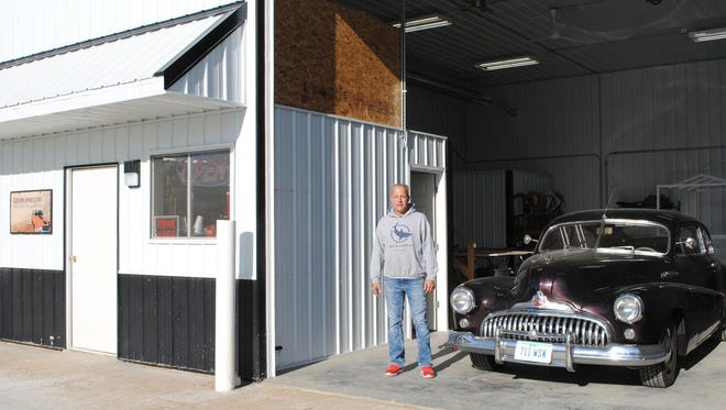 John Griffith, owner of Custom Upholstery, stands next to a customer's vintage automobile at the business' new location at 440 Hawkeye Dr., Suite D, Williamsburg.