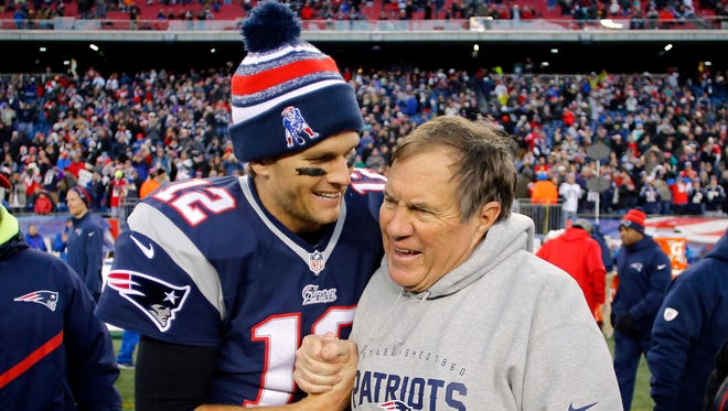 New England Patriots quarterback Tom Brady (12) celebrates with head coach Bill Belichick (R) after clinching the AFC East title last month.