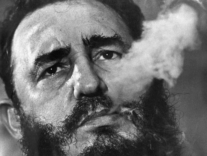 Fidel Castro exhales cigar smoke during a March 1985