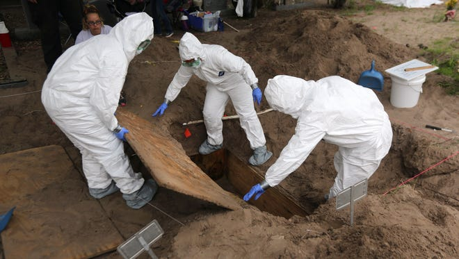A forensic anthropology team unearths the remains of unidentified immigrants from a cemetery on May 21, 2013 in Falfurrias, Texas. Teams from Baylor University and the University of Indianapolis are exhuming the bodies of more than 50 immigrants who died, mostly from heat exhaustion, while crossing illegally from Mexico into the United States. The bodies will be examined and cross checked with DNA sent from Mexico and Central American countries, with the goal of reuniting the remains with families. In Brooks County alone, at least 129 immigrants perished in 2012, the highest rate in the United States, according to forensic anthropologists.
