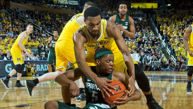 Michigan State guard Cassius Winston, bottom, tries to keep the ball away from Michigan guard Zak Irvin (21), in the first half of an NCAA college basketball game at Crisler Center in Ann Arbor, Mich., Tuesday, Feb. 7, 2017. (AP Photo/Tony Ding)
