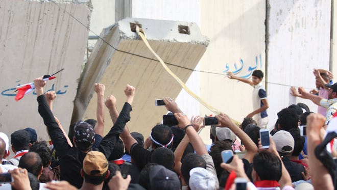"""Iraqi protesters open a breach in a concrete wall surrounding the parliament after breaking into Baghdad's heavily fortified """"Green Zone"""" on April 30, 2016."""